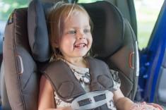 uśmiechnięte dziecko w foteliku samochodowym